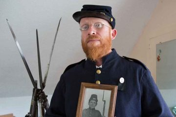 Civil war re-enactor preparing to take part in the 150th  anniversary of the Battle of Gettysburg.  He holds a photo of his great-great-great-grandfather who fought in the war. (Lindsay Lazarski/WHYY)