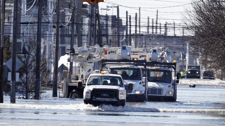 Crews drive a caravan of utility repair trucks on flooded streets early Sunday, Jan. 24, 2016, in Sea Isle City, N.J.  (AP Photo/Mel Evans)