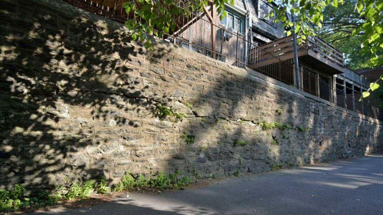Sections of a 550-foot-long retaining wall in the East Falls neighborhood of Philadelphia are leaning, cracked, and unsafe, affecting the owners of 65 homes on either side of the wall. (Bas Slabbers/for NewsWorks, file photo)