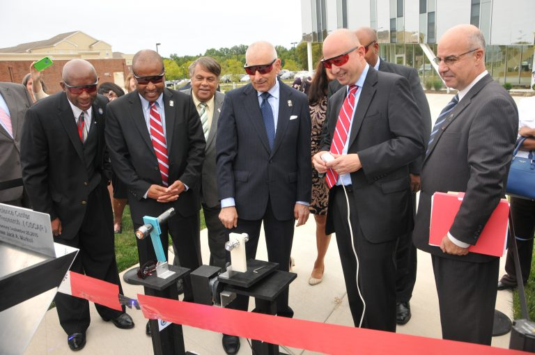 Governor Jack Markell (second from right) cuts the ceremonial ribbon using a laser. (Photo courtesy of Delaware State University)