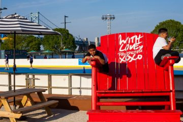 Jeiemai Floyd,7, at left and his brother Elyjah Floyd,12, hang out on the oversized chair at the River Rink at Penn's Landing. (Brad Larrison for NewsWorks)