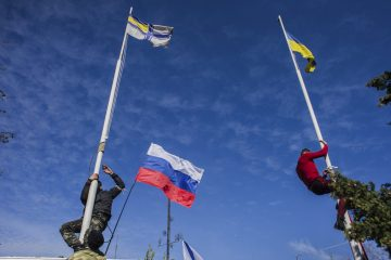 Members of the Crimean pro-Russian self-defense forces climb up to remove a Ukrainian flag, right, and a Ukrainian navy flag, left, at the Ukrainian navy headquarters in Sevastopol, Crimea, Wednesday, March 19, 2014. In center is a Russian flag. (AP Photo/Andrew Lubimov)