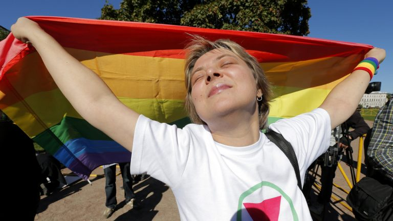 Gay rights activist Natalia Tsybalova, holds a rainbow flag during a picket in downtown St. Petersburg, Russia, Friday, Sept. 6, 2013. (AP Photo/Dmitry Lovetsky)