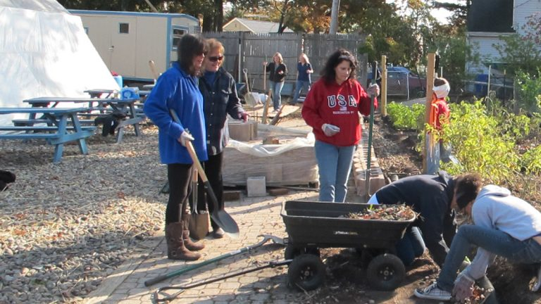 Volunteers help build a wall at a community garden at Sandy Service Day project in Brick Township (photo by Phil Gregory).