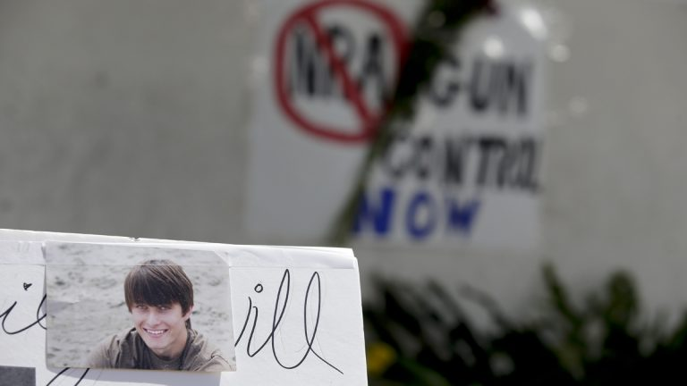 Images of Chrisotper Ross Michael-Martinez are displayed as part of a makeshift memorial in front of the IV Deli Mart, where part of Friday night's mass shooting took place by a drive-by shooter in the Isla Vista area near Goleta, Calif. (AP Photo/Chris Carlson)