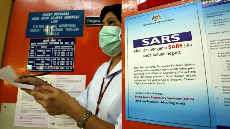 A hospital worker wears a surgical mask to protect herself from severe acute respiratory syndrome