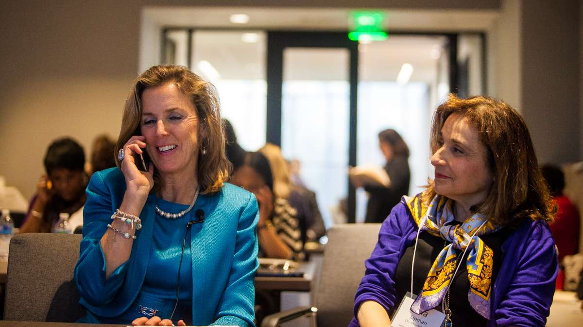 Katie McGinty, chief of staff to Gov. Tom Wolf, speaks with the recipient of a scholarship Thursday after calling his home. At her right is Ina Lipman, executive director of the scholarship fund. (Brad Larrison/for NewsWorks)