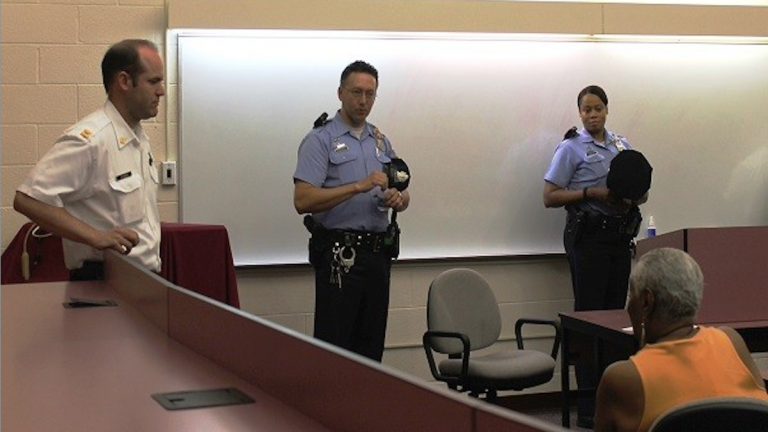 Capt. John Fleming and Officers Thomas Seymour and Kim Harris speak with residents at A PSA-4 meeting in May. (Matthew Grady for NewsWorks)