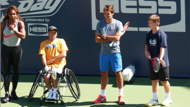Kyle Seelig (right), who represented East Falls' Legacy Youth Tennis and Education at Arthur Ashe Youth Day at the U.S. Open, competed against Serena Williams, Roger Federer and the winner of wheelchair-tennis competition in a target-hitting competition last Saturday. (Photo courtesy of the U.S. Open)