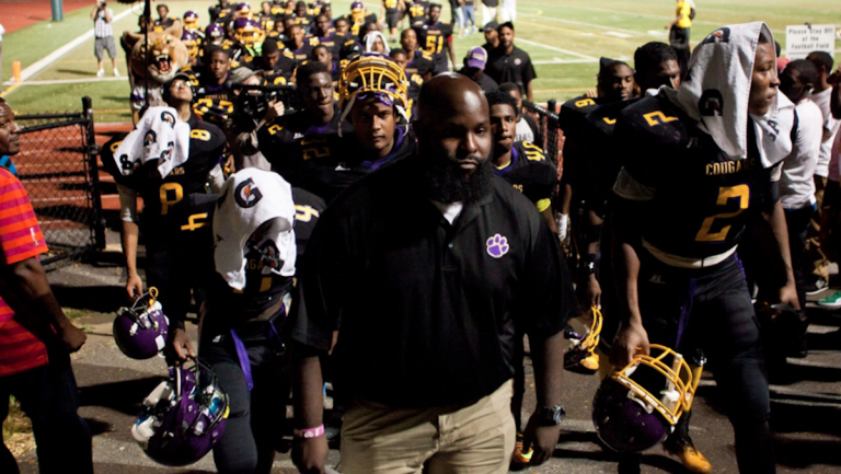 Head Coach Edward Dunn leads his MLK High School Cougars football team off the field after a disappointing 20-16 loss to Mastery Charter on Friday. (Brad Larrison/for NewsWorks)