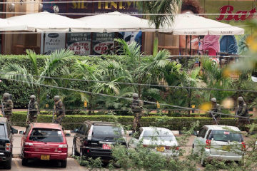 A line of soldiers from the Kenya Defense Forces run in front of the Westgate Mall in Nairobi on Sunday. Multiple barrages of gunfire erupted Sunday morning from the upscale Kenyan mall where there is a hostage standoff with Islamic extremists nearly 24 hours after they attacked using grenades and assault rifles. (AP Photo/Ben Curtis)