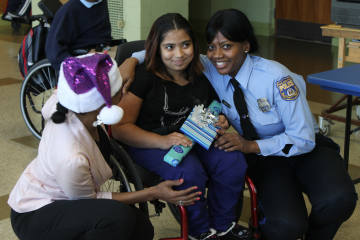 Widener Memorial School student Alicia Rodriguez receives a gift from 35th District Community Relations Officer Roslyn Downing. (Matthew Grady/for NewsWorks)