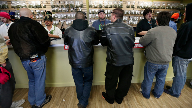 Employees help customers at the crowded sales counter inside the Medicine Man marijuana retail store in Denver. But is legalization the best path? (AP Photo/Brennan Linsley, File)