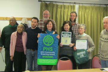 Recipients posed with the blue-and-green sign that touts the Vernon Park rain garden for
