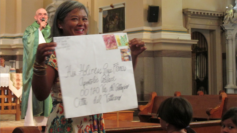 With Father Sy Paterka in the background, Maria Beatty holds an oversized envelope in which letters inviting Pope Francis to Germantown will be mailed. (Photo courtesy of St. Vincent de Paul Parish)