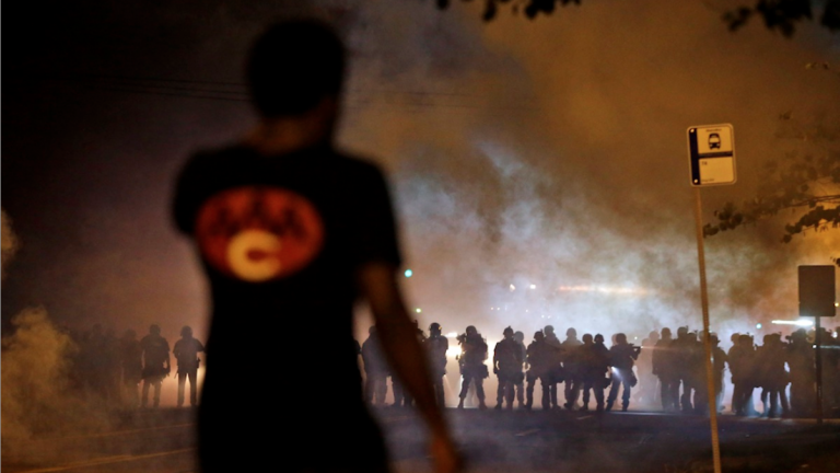 A man watches as police walk through a cloud of smoke during a clash with protesters in Ferguson, Mo. (AP Photo/Jeff Roberson)