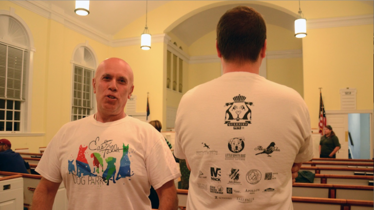 Jim Guaneri (left) and and Joe Silvent show off $10 shirts designed by East Falls Community Council to help raise funds for a proposed dog park. (Jimmy Viola/for NewsWorks)