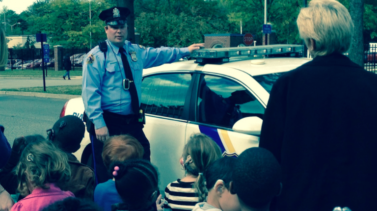 Officer Matt McCuen brought along a 14th District police cruiser for the Clarke Schools students to check out. (Brian Hickey/WHYY)