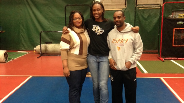 Kayla Thomas stands on the Mastery basketball court with her mother Keturah Thomas and coach Antowine Graham. (Desirae Holland/for NewsWorks)