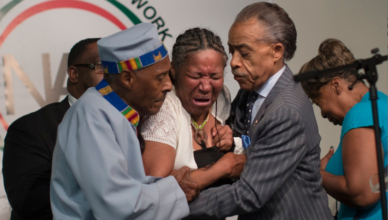 Esaw Garner, wife of Eric Garner, breaks down in the arms of Rev. Herbert Daughtry, center, and Rev. Al Sharpton, right, during a July rally at the National Action Network headquarters for Eric Garner. (AP Photo/John Minchillo)