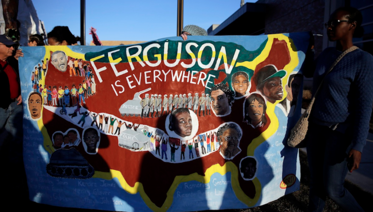 People hold up a sign during a protest outside the Ferguson (Mo.) Police Department on Monday. Protesters marched several miles through Ferguson to the police department from the site where Michael Brown was killed this past summer by a police officer. (AP Photo/Jeff Roberson)