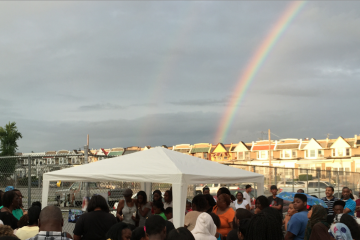 A rainbow in the sky behind Wednesday night's vigil for homicide victim DeeAnna Riddle. (Brian Hickey/WHYY)