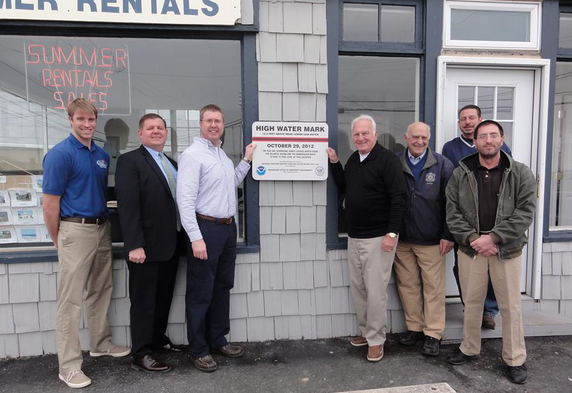 Officials at the unveiling of a high mark mark sign at Wood Agency in Manasquan. Pictured (l to r): Christopher Huch, Community Resiliency Specialist from the Jacques Cousteau Research Reserve; Owen McCarthy, Councilman & Chair of the Public Safety Committee; Ray Krudzlo, Senior Service Hydrologist, National Weather Service Forecast Office Mount Holly; Robert Wood, Owner, Wood Agency; George Dempsey, Mayor; Joseph Bossone, Concilman & OEM Liaison; and Joseph Miketta, Warning Coordination Meteorologist, National Weather Service Forecast Office Mount Holly. (Photo courtesy of the Manasquan Office of Emergency Management)