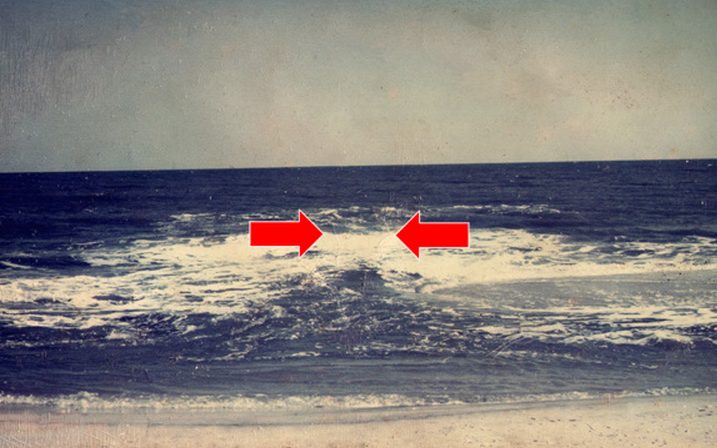 In this NOAA photo, the rip current is surging seaward in the area between the red arrows.
