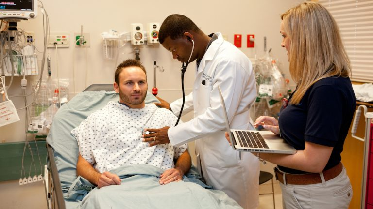 A scribe enters patient data into a laptop while a doctor performs an examination. (Image courtesy of Scribe America)