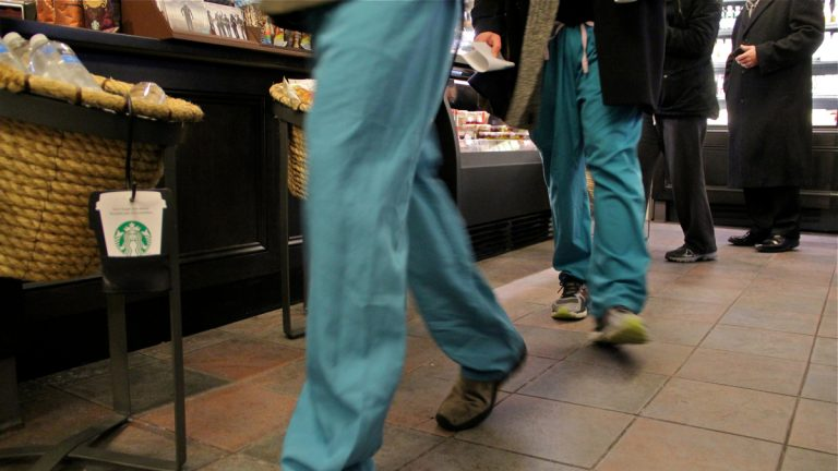Hospital workers wear their scrubs into a coffee shop at 10th and Chestnut streets in Philadelphia. (Emma Lee/WHYY)