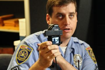 SEPTA Transit Police Sergeant Timothy Catto demonstrates how a new body-mounted camera works. Three SEPTA officers will be testing the cameras this week. (Kimberly Paynter/WHYY)