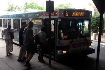 Passengers board the Manayunk-bound 61 bus at Market and 9th streets in Center City. (Eric Walter/WHYY)