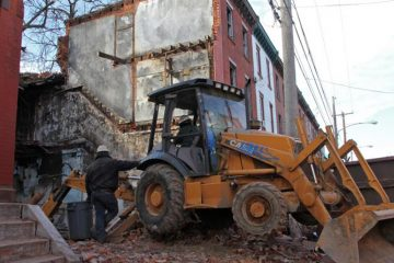 Workers demolish a North Philadelphia rowhouse. (Emma Lee/WHYY)