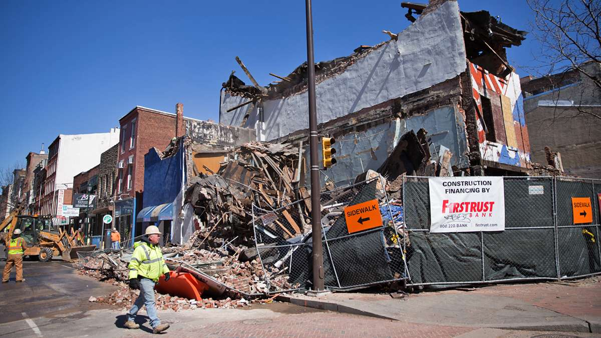 Brick and debris landed in the street after a side wall collapsed during the demolition of the Shirt Corner on 3rd and Market Streets Thursday afternoon (Lindsay Lazarski/WHYY)