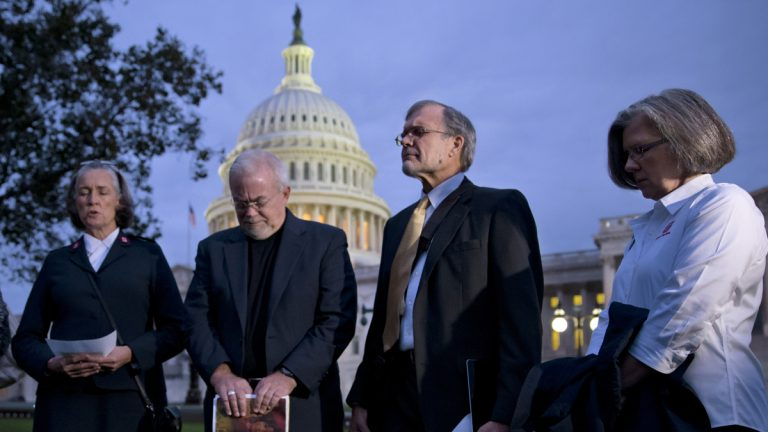 With time growing desperately short for Congress to prevent a threatened Treasury default and stop a partial government shutdown, a group of ministers, the Circle of Protection, pray at dawn at the Capitol to draw attention to lawmakers that political divisiveness hurts the most vulnerable Americans, in Washington, Tuesday, Oct. 15, 2013. From right: Kathy Saile, Gary Cook, Rev. Jim Wallis, and Major Carole Busroe of the Salvation Army. (AP Photo/J. Scott Applewhite)