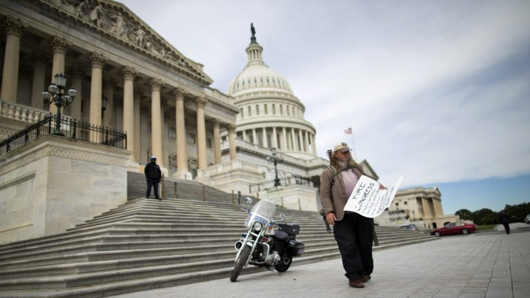 Rick Hohensee of Washington holds a 'Fire Congress' sign near the House steps on Capitol Hill in Washington, Tuesday, Oct. 8, 2013 (Evan Vucci/AP Photo)