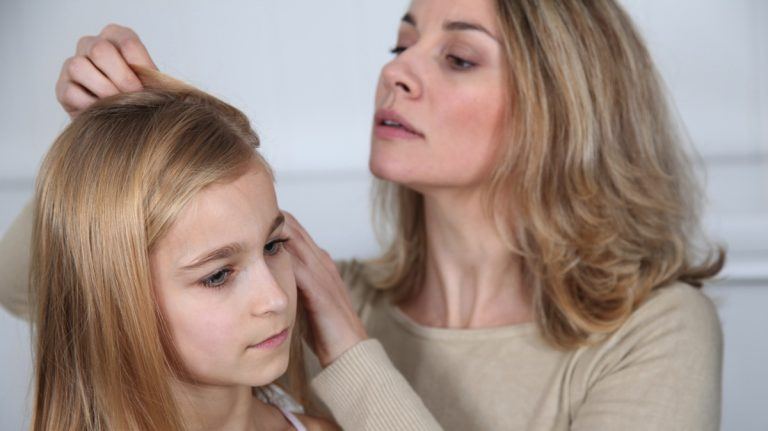 Mother treating daughter's hair against lice image courtesy of Shutterstock.com