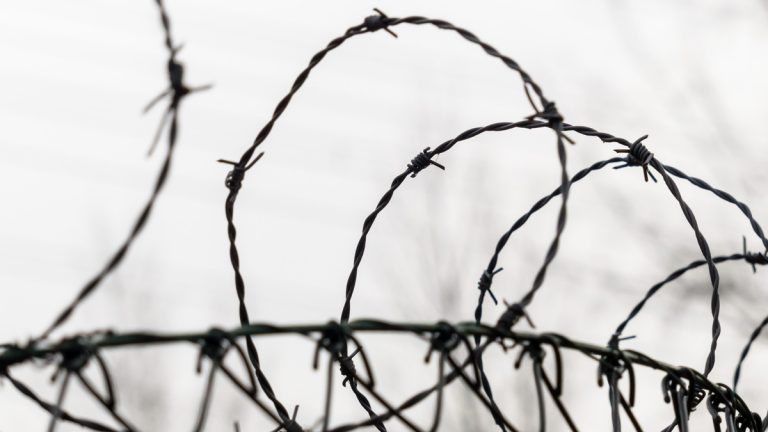 (<a href='http://www.shutterstock.com/pic-171287141/stock-photo-a-fence-is-secured-with-barbed-wire-symbolic-photo-for-security-prison-and-crime.html'>Barbed wire</a> image courtesy of Shutterstiock.com)