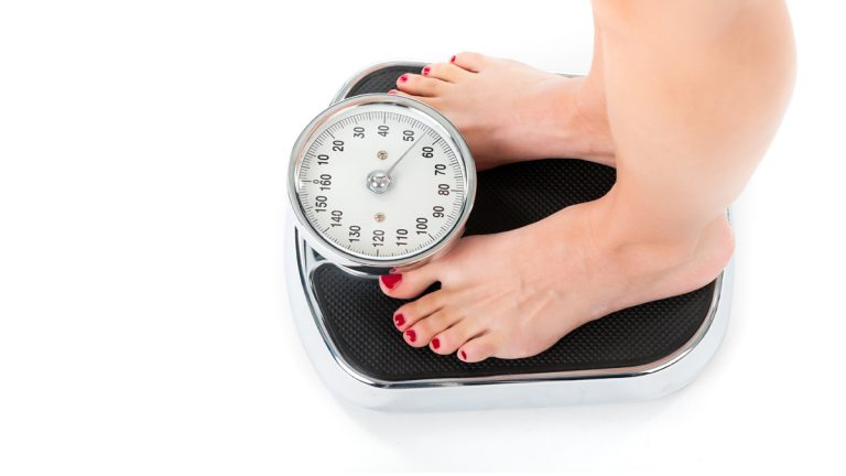 (<a href='http://www.shutterstock.com/pic-117752179/stock-photo-diet-and-weight-young-woman-standing-on-a-scale-only-feet-to-be-seen.html?src=csl_recent_image-1&ws=1'>Scale image</a> courtesy of Shutterstock.com)