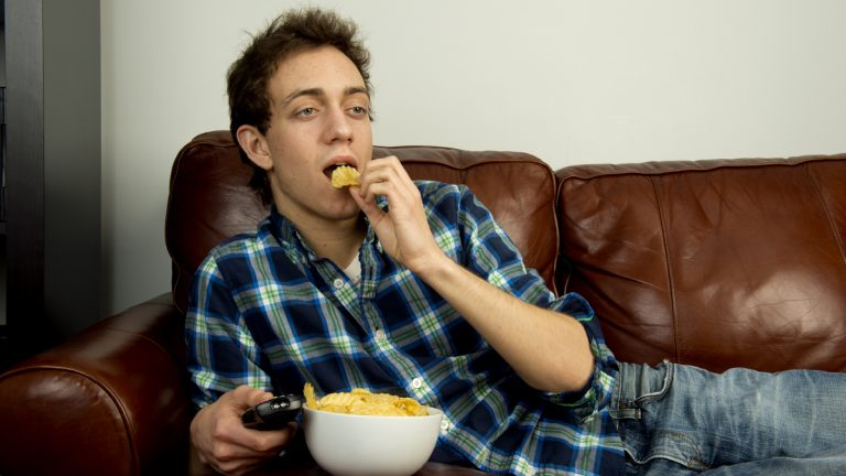 (<a href='http://www.shutterstock.com/pic-127777754/stock-photo-young-man-on-couch-eating-potato-chips.html'>Young man on the couch image</a> courtesy of Shutterstock.com)