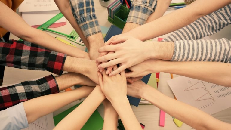 (<a href=`http://www.shutterstock.com/pic-298084979/stock-photo-united-hands-of-business-team-on-workspace-background-top-view.html'>Friends at work</a> image courtesy of Shutterstock.com)