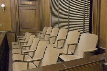 (<a href='http://www.shutterstock.com/pic-121502677/stock-photo-side-view-of-a-empty-jury-box-in-the-courthouse.html'>Jury box image</a> courtesy of Shutterstock.com)