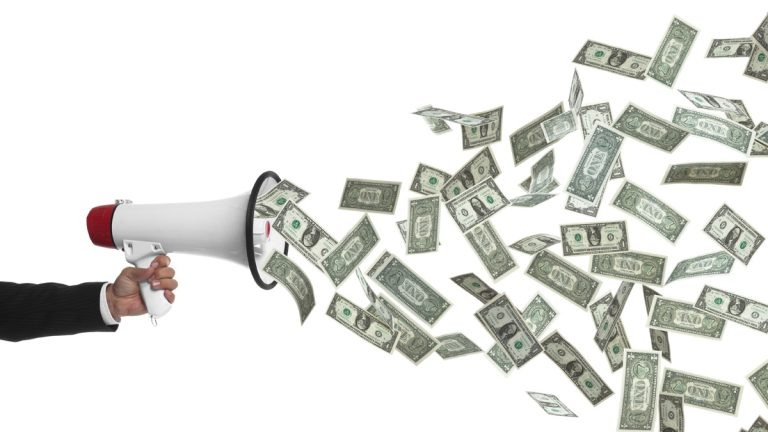 (<a href='http://www.shutterstock.com/pic-173853539/stock-photo-arm-holding-megaphone-speaking-money-money-talks.html'>Money talks</a> image courtesy of Shutterstock.com )