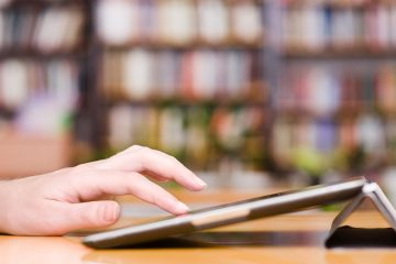 (<a href='http://www.shutterstock.com/pic-172423823/stock-photo-hands-typing-on-tablet-computer-in-library.html'>Modern library image</a> courtesy of Shutterstock.com)