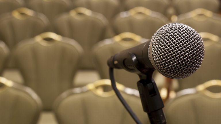 (<a href='http://www.shutterstock.com/pic-79228525/stock-photo-microphone-in-front-of-several-rows-of-empty-chairs-with-shallow-depth-of-field.html'>Microphone</a> image courtesy of Shutterstock.com)