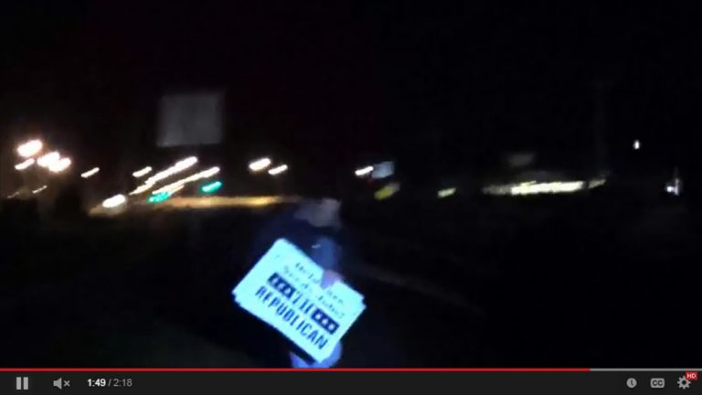 This still from video posted on YouTube shows a man taking Republican signs. (YouTube)
