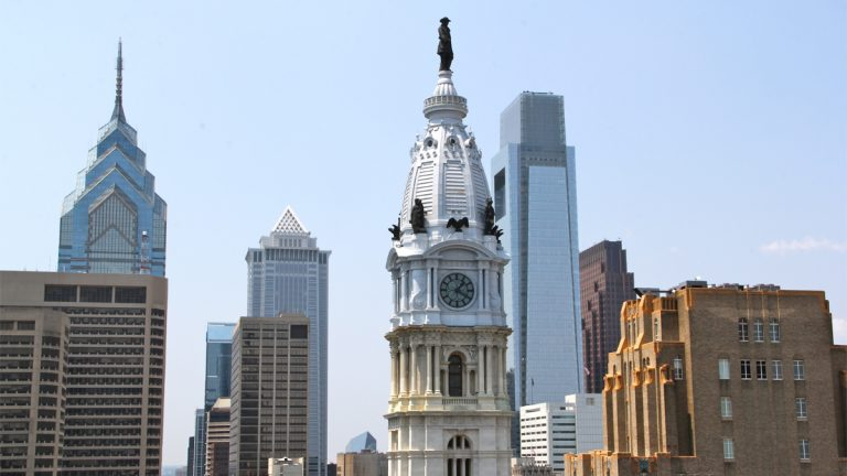 A statue of William Penn atop Philadelphia's City Hall can be seen in the forefront of a portion of the city's skyline (NewsWorks Photo, file)