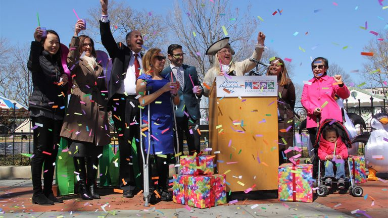 Officials raise a cake shake to toast Franklin Square's 10th re-birthday party. (Emma Lee/WHYY)