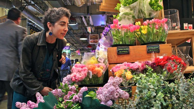 At Market Blooms in Reading Terminal Market Anndee Hochman attempts to smell the aromas of lilac and eucalyptus. (Emma Lee/for NewsWorks)
