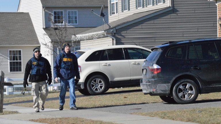 Investigators walk outside the Hamilton's Smyrna house looking for clues. (John Jankowski/WHYY)
